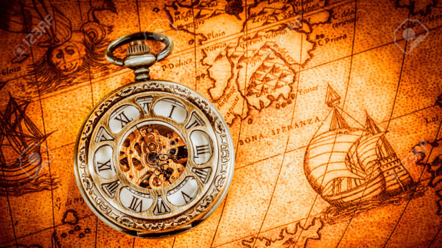 Vintage Antique pocket watch on an ancient world map in 1565..